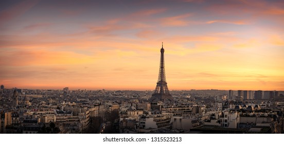Panoramic aerial view of Paris, France, with the Eiffel Tower and the many city rooftops at sunset. Very High Resolution.
