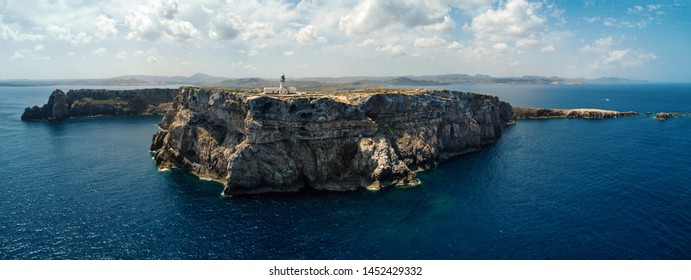 Panoramic aerial view of rocky coastline with Cape Cavalleria Lighthouse. Menorca, one of the Balearic Islands located in the Mediterranean Sea belonging to Spain.
