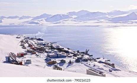 The panoramic aerial view of russian (soviet) Barentsburg, Svalbard. Snow mountain peaks on the horizon, the whole village view from the top of the hill, silence and calm of the sunny day, background.