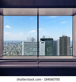 Panoramic aerial view of Shinjuku financial district skyscrapers through a window frame. Tokyo, Japan, Asia