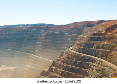 Panoramic aerial view of Super Pit goldmine in Kalgoorlie, Western Australia, with trucks on winding path along edges of the whole, heavy machinery, summer sunny dusty blue sky.