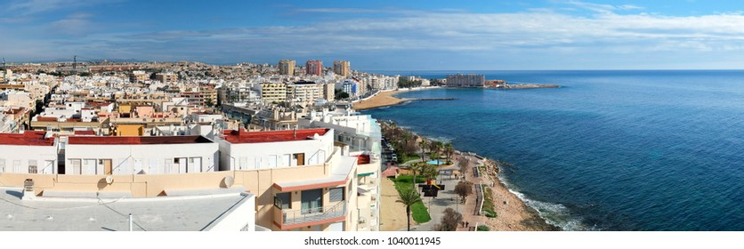 Panoramic aerial view of Torrevieja city popular travel destination for tourists. Rooftops of residential coastal houses and idyllic blue tranquil smooth sea Costa Blanca. Province of Alicante. Spain