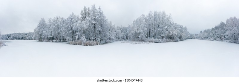 Panoramic aerial view of winter beautiful landscape with trees covered with hoarfrost and snow. Winter scenery from above. Landscape photo captured with drone.