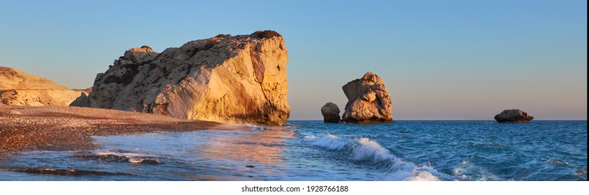 Panoramic Aphrodite rock Cyprus in soft evening light, curvy waves in the foreground touristic attraction of so called love rock - Shutterstock ID 1928766188