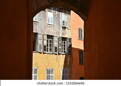 Panoramic arch view of traditional old houses with ochre stucco walls and wooden window shutters in the historic center of Grasse in French Riviera, Provence-Alpes-Côte d'Azur, France.