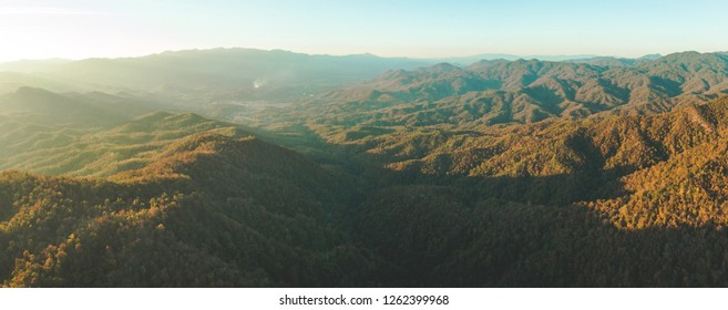Panoramic autumn overview. North Thailand mountain valley. Aerial drone shot. Breathtaking scenery of orange colored sunlit hills. Beauty of wild untouched virgin nature. Exotic travel. Wilderness.