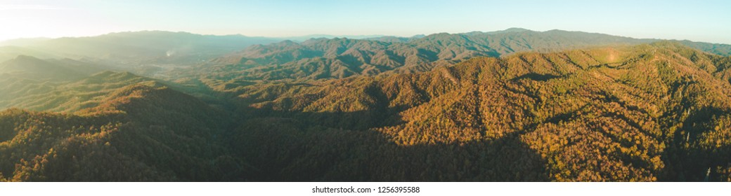Panoramic autumn overview of Thailand valley. Aerial drone shot. Breathtaking scenery of orange colored sunlit hills. Beauty of wild untouched virgin nature. Exotic travel. Wilderness.
