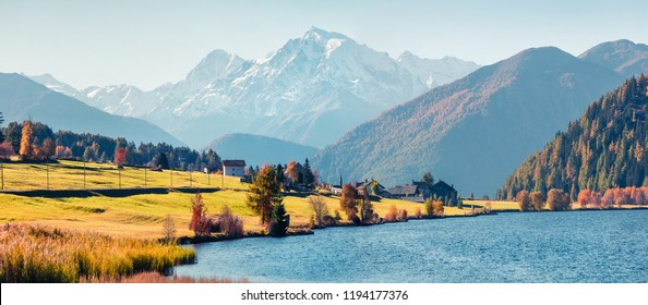 Panoramic autumn scene of Haidersee (Lago della Muta) lake with Ortler peak on background. Splendid morning view of Italian Alps, Italy, Europe.Beauty of nature concept background.
