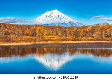 Panoramic autumn  view of the  Koryaksky Volcano reflected in the water of the lake. Russian Far East, Kamchatka Peninsula
