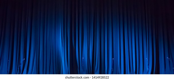 Panoramic Background of blue curtain on stage of theater. Closed curtain of stage in the spotlight before the show. Wide Angle Wallpaper, billboard or Web banner With Copy Space