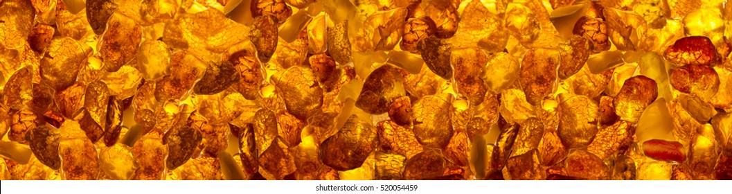 panoramic background  closeup luminous  baltic amber stones rectangular lie on a flat surface
