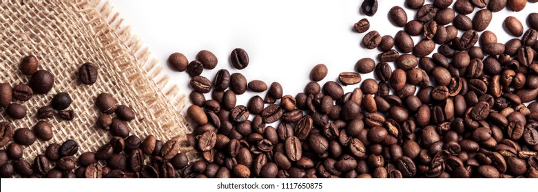 Panoramic background of spilled coffee beans on a white background with a jute sack