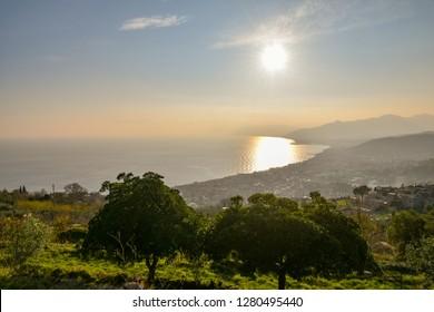 Panoramic backlight view of the western Ligurian coast with the cities of Pietra Ligure and Albenga, Liguria, Italy