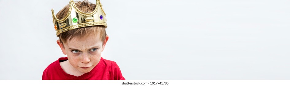 panoramic banner of angry beautiful spoiled kid with frowning freckles wearing a king crown for mad attitude facing unhappy parenthood and education, white background, copy space