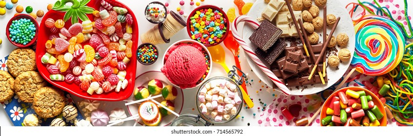 Panoramic banner with an assorted colorful candy, chocolate, cookies and ice cream for a kids birthday party in a full frame background view
