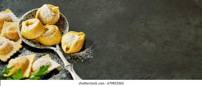 Panoramic banner with fresh handmade Italian tortellini pasta and ravioli on an old vintage spoon with copy space on a grey textured surface