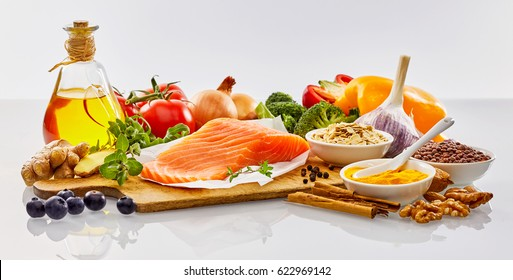 Panoramic banner with fresh healthy food for the heart and cardiovascular system with nuts, herbs, salmon, spices, bell peppers, tomatoes, broccoli, garlic, olive oil and blueberries on white