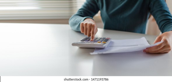 panoramic banner. hand of young woman using calculator for calculating family budget cost bills on desk in home office, plan money cost saving, investment, business finance, expenses, income concept