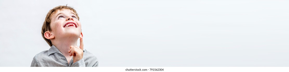 panoramic banner of happy imaginative little boy looking away, pointing his finger up for concept of adorable kid curiosity, open-mindedness and future, white background, copy space