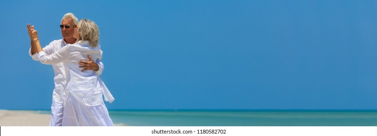 Panoramic banner image of happy senior man and woman couple dancing and holding hands on a deserted tropical beach with turquoise sea and clear blue sky