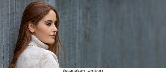 Panoramic banner image outdoor portrait of beautiful girl or young woman looking thoughtful with red hair wearing a white jumper