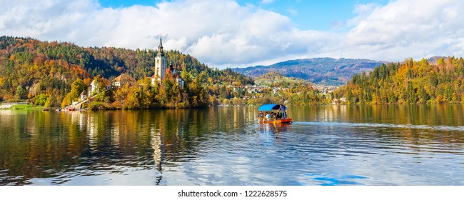 Panoramic banner of Lake Bled with Church and Pletna boat, Slovenia and autumn colorful trees background