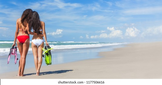 Panoramic banner rear view of two beautiful young women in red and white bikinis with snorkel, mask & flippers embracing on a deserted beach with blue sky