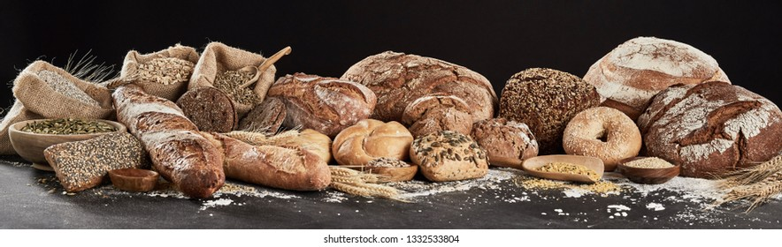 Panoramic banner with rustic bread assortment, decorated with seeds, cereal and flour, sitting on dark surface against white background