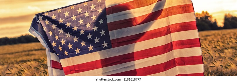 Panoramic banner silhouette of African American girl teenager female young woman in field of wheat or barley crops holding USA stars and stripes flag in golden sunset evening sunshine