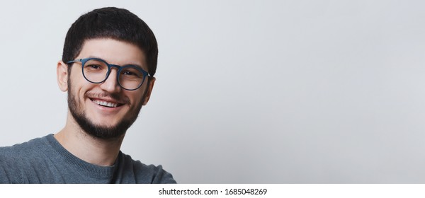 Panoramic banner, studio portrait of young smiling guy wearing round eyeglasses on white background with copy space.