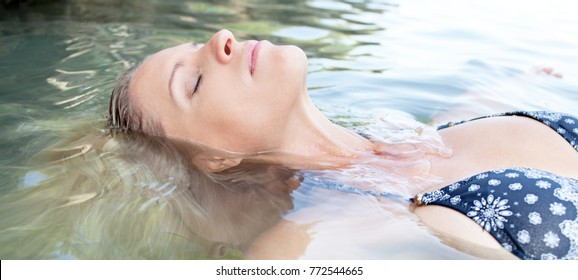 Panoramic beauty portrait of beautiful tourist woman floating in clear sea water, relaxing eyes closed, summer holiday, nature outdoors. Female bathing swimming, exotic travel recreation lifestyle.