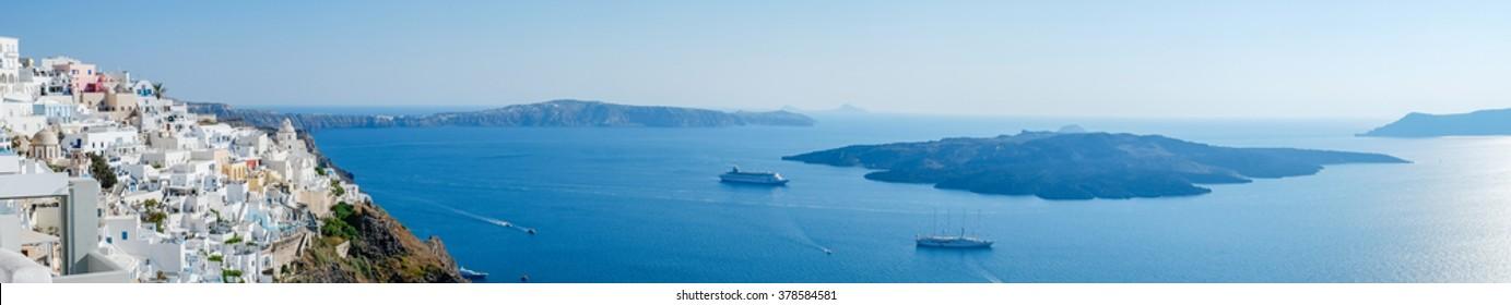 Panoramic bird eye aerial view of white building, blue sky and vivid sea in Santorini island, Oia, Greece