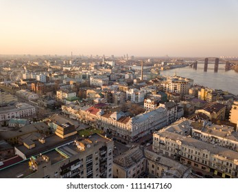 The panoramic bird's eye view from drone to the central historical part of the city Kiev - the Podol district, the Dnieper River in Kiev, Ukraine at summer sunset.