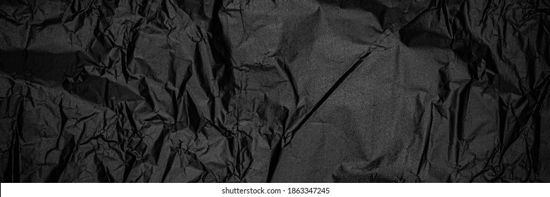 Panoramic black crumbled paper texture. Dark wrapping paper. Black destressed paper structure, banner