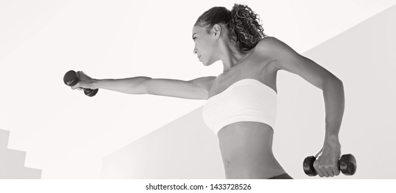 Panoramic black and white portrait of beautiful young woman in graphic white walls space outdoors, lifting weights on sport training exercise fitness. Athlete, leisure recreation healthy lifestyle.
