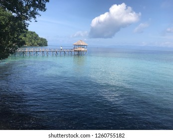 Panoramic blue watercolor beach with a long wooden bridge and floating house in Ambon Indonesia