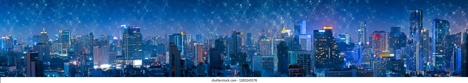 Panoramic building modern business district at night with lines and dots of connection in the sky. Wireless internet network in smart city.