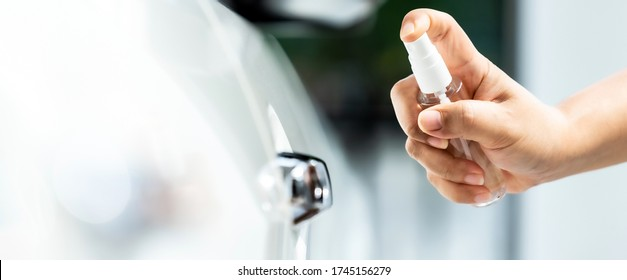 panoramic of car vehicle sterilization cleaning using hand spraying alcohol, disinfectant spray on cdoor handle for safety prevent protect from virus and germ infection Covid-19 coronavirus pandemic.