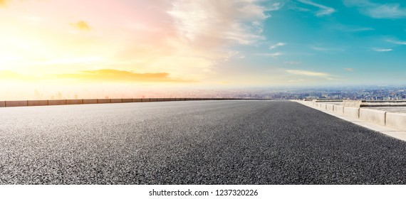 Panoramic city skyline and buildings with empty asphalt road at sunset