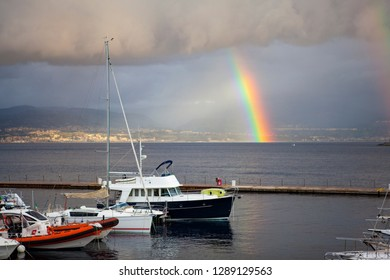 Panoramic. City view. The central port (harbour) of the city of Messina with yachts and small boats on a cloudy day with a rainbow with the view on Reggio Calabria. Messina. Sicily. Italy
