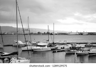 Panoramic. City view. The central port (harbour) of the city of Messina with yachts and small boats on a cloudy day with the view on Reggio Calabria. Black and White. Messina. Sicily. Italy