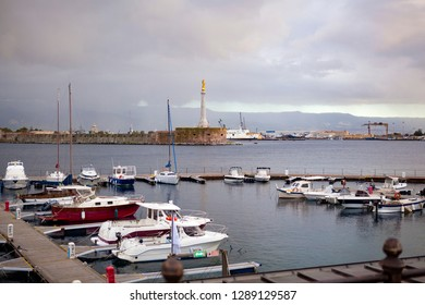 Panoramic. City view. The central port (harbour) of Messina with golden statue of st. Madonna, yachts, small boats, and ships on a cloudy day with the view on Reggio Calabria. Messina. Sicily. Italy