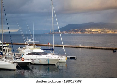 Panoramic. City view. The central port (harbour) of the city of Messina with yachts and small boats on a cloudy day with a golden sunshine with the view on Reggio Calabria. Messina. Sicily. Italy