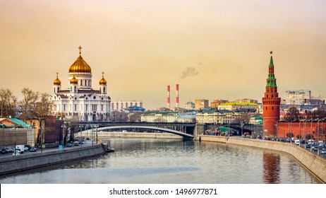 Panoramic cityscape with beautiful Cathedral of Christ the Saviour and Kremlin Vodovzvodnaya Tower view from Moskva River golden sunrise Moscow Russia
