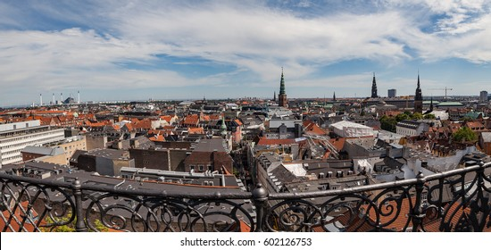 Panoramic cityscape of Copenhagen from the Round Tower. Old churches towers and roof reconstruction of city center. Fence at the foreground