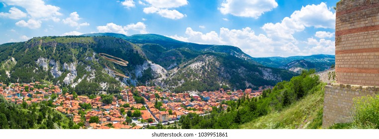 Panoramic cityscape view from historical Kutahya Castle with brick stone walls and bastions on cloudy blue sky background in Turkey.