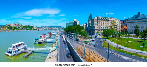 Panoramic cityscape view of hungarian capital city of Budapest from Elisabeth Bridge. The quay of river Danube. Summertime sunshine day, blue sky and green of trees.