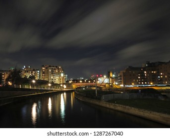 panoramic cityscape view of leeds at night from the river aire with crown point bridge and apartments reflected in the water and parish church illuminated behind modern developments