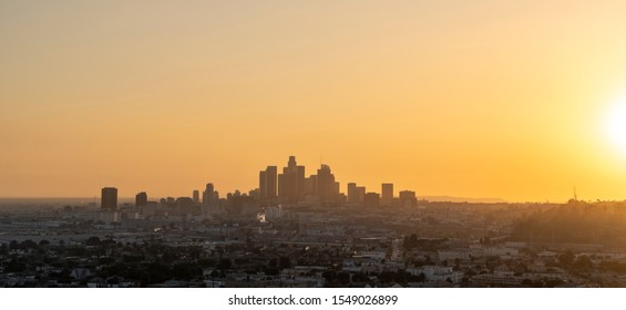 Panoramic cityscape view of sunset over Los Angeles, California, USA. The sky is yellow and hazy from nearby wild fire smoke and smog from traffic. Tower blocks and skyscrapers dominate the sky line.