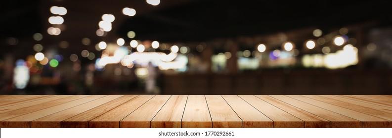 Panoramablick auf leerem, leerem, sauberem Holztisch auf unscharfem Hintergrund des Straßencafé-Nachtcafés Verwendung für die Montage der dunklen Szene im Pub-Café, unscharfe breite Holzkonfektionsbar in luxuriöser Küchenhintergrund